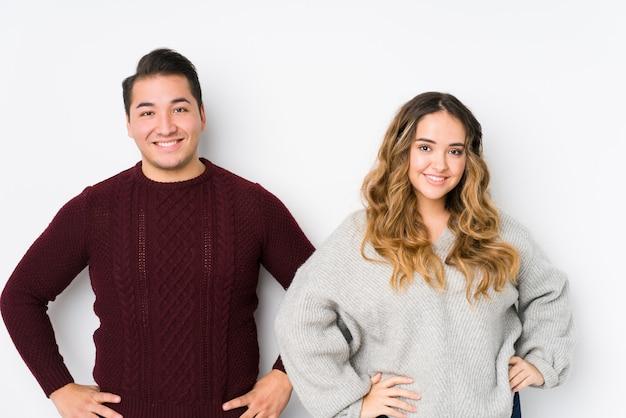 Jeune couple posant dans un mur blanc confiant en gardant les mains sur les hanches.