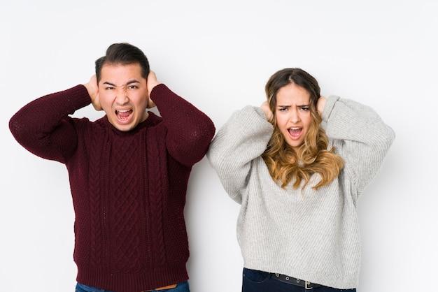 Jeune couple posant dans un mur blanc couvrant les oreilles avec les mains en essayant de ne pas entendre un son trop fort.