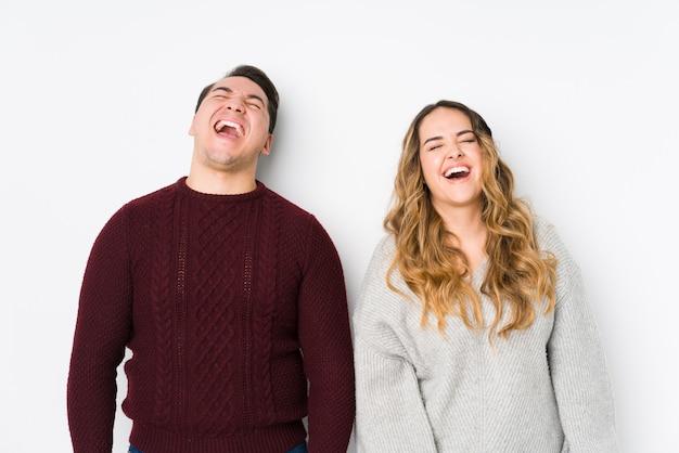 Jeune couple posant dans un mur blanc détendu et heureux de rire, cou tendu montrant les dents.