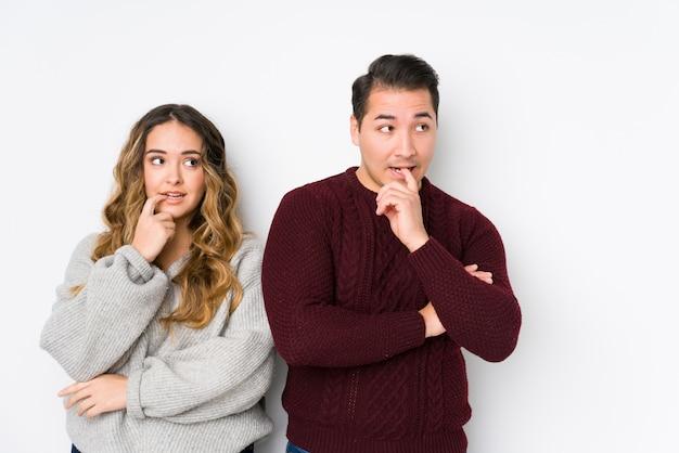 Jeune couple posant dans un mur blanc détendu en pensant à quelque chose en regardant un espace copie.