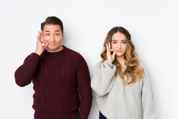 Jeune couple posant dans un mur blanc avec les doigts sur les lèvres gardant un secret.