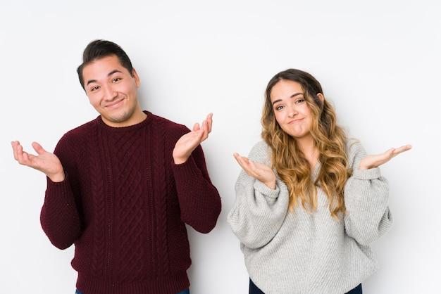 Jeune couple posant dans un mur blanc, doutant et haussant les épaules en remettant en question le geste.