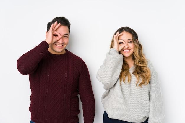 Jeune couple posant dans un mur blanc excité en gardant le geste correct sur l'oeil.