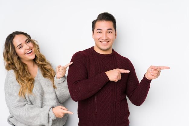 Jeune couple posant dans un mur blanc excité pointant avec les index loin.