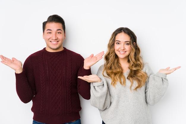 Jeune couple posant dans un mur blanc fait l'échelle avec les bras, se sent heureux et confiant.