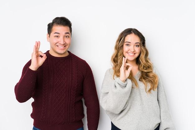Jeune couple posant dans un mur blanc gai et confiant montrant un geste correct.