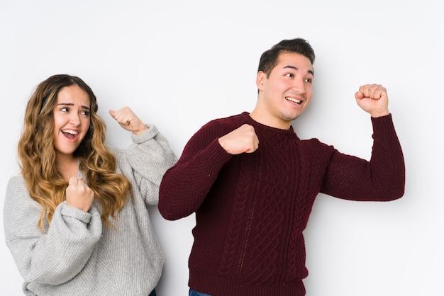 Jeune couple posant dans un mur blanc levant le poing après une victoire, concept gagnant.