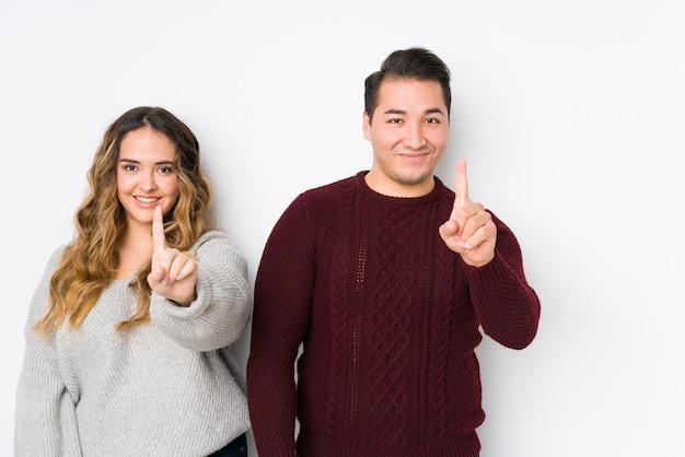 Jeune couple posant dans un mur blanc montrant le numéro un avec le doigt.