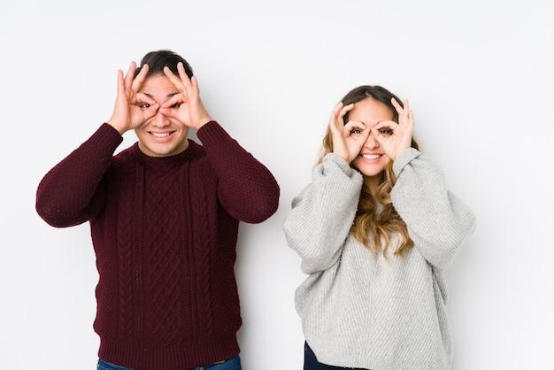 Jeune couple posant dans un mur blanc montrant un signe correct sur les yeux
