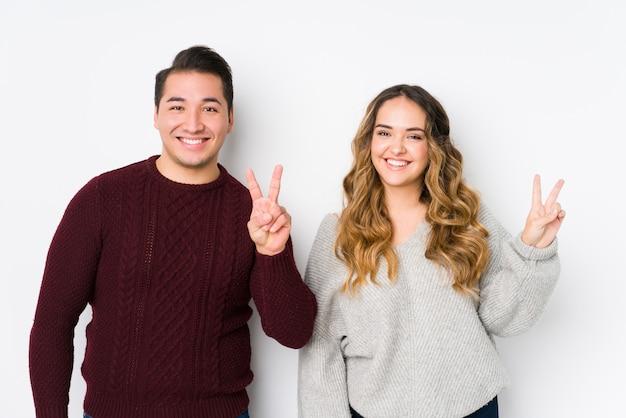 Jeune couple posant dans un mur blanc montrant le signe de la victoire et souriant largement.