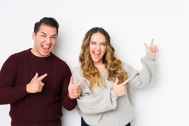 Jeune couple posant dans un mur blanc pointant avec des index vers un espace de copie, exprimant l'excitation et le désir.