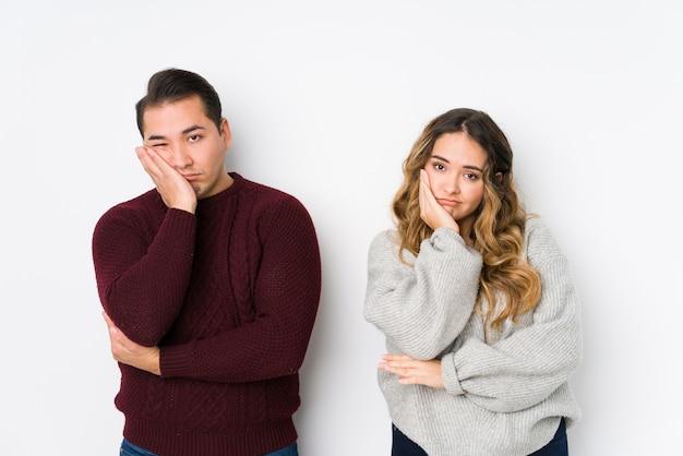Jeune couple posant dans un mur blanc qui s'ennuie, fatigué et a besoin d'une journée de détente.