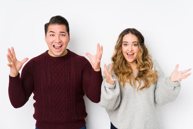 Jeune couple posant dans un mur blanc recevant une agréable surprise, excité et levant les mains.