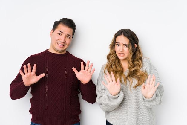 Jeune couple posant dans un mur blanc rejetant quelqu'un montrant un geste de dégoût.