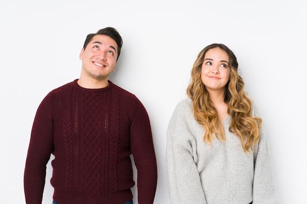 Jeune couple posant dans un mur blanc rêvant d'atteindre des buts et des objectifs