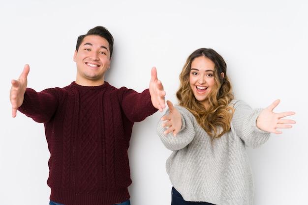 Jeune couple posant dans un mur blanc se sent confiant en donnant un câlin à la caméra.
