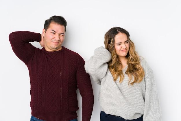 Jeune couple posant dans un mur blanc souffrant de douleurs au cou en raison d'un mode de vie sédentaire.