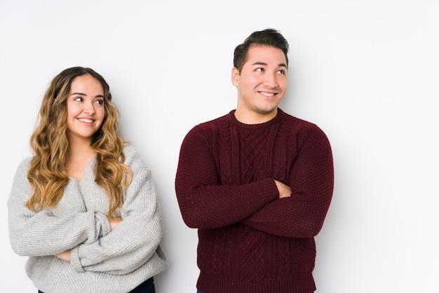 Jeune couple posant dans un mur blanc souriant confiant avec les bras croisés.