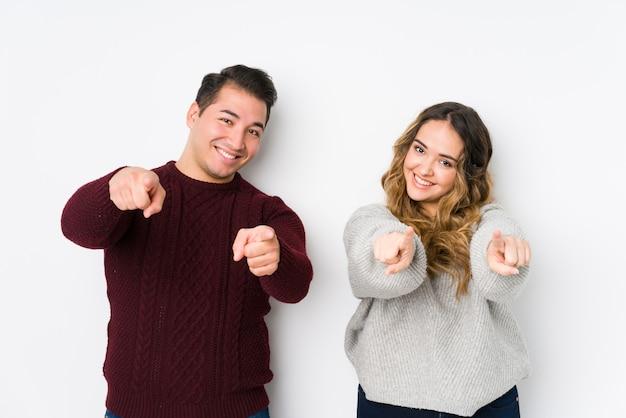 Jeune couple posant dans un mur blanc sourires joyeux pointant vers l'avant.
