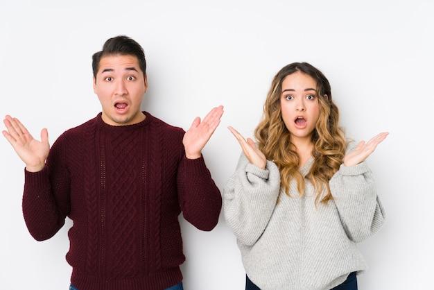 Jeune couple posant dans un mur blanc surpris et choqué.