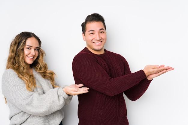 Jeune couple posant dans un mur blanc tenant un espace copie sur une paume.