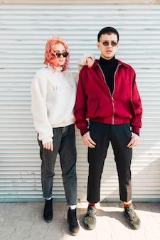 Jeune couple posant debout près des stores de la porte