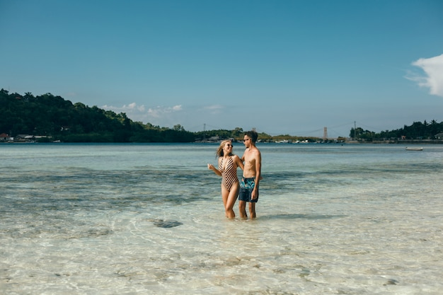 Jeune couple posant sur la plage, s'amusant dans la mer, riant et souriant