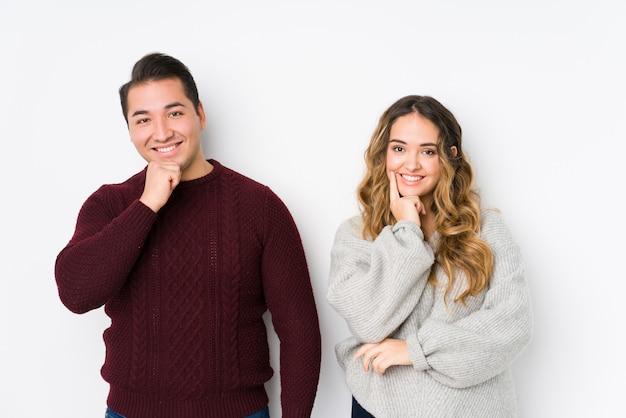 Jeune couple posant souriant heureux et confiant, touchant le menton avec la main.