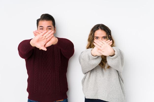 Jeune couple, poser, dans, a, mur blanc, faire, a, déni, geste