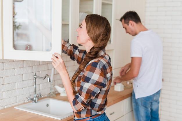 Jeune couple positif, faire du thé dans la cuisine à la maison