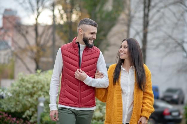 Jeune couple positif se regardant tout en se promenant ensemble