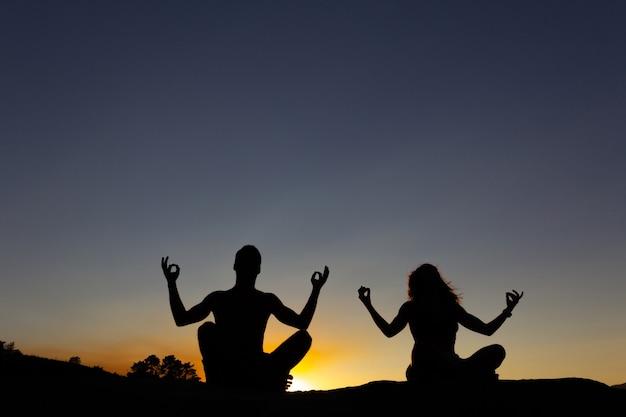 Jeune couple pratiquant le yoga au coucher du soleil. rétro-éclairage. espace de copie.