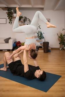 Jeune couple pratiquant le yoga ensemble à la maison dans un intérieur moderne. passe-temps, convivialité, mode de vie sain