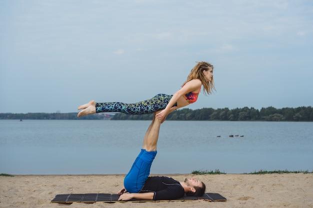 Jeune couple, pratiquer, yoga, sur, ville, arrière-plan