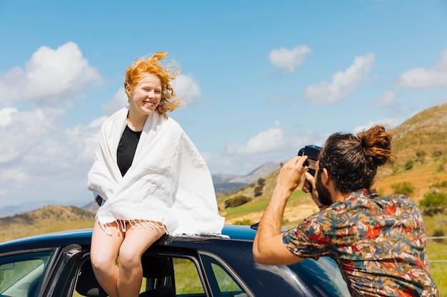 Jeune couple prenant des photos en plein air