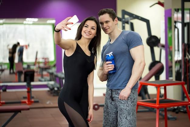 Jeune couple prenant un sefie dans une salle de sport