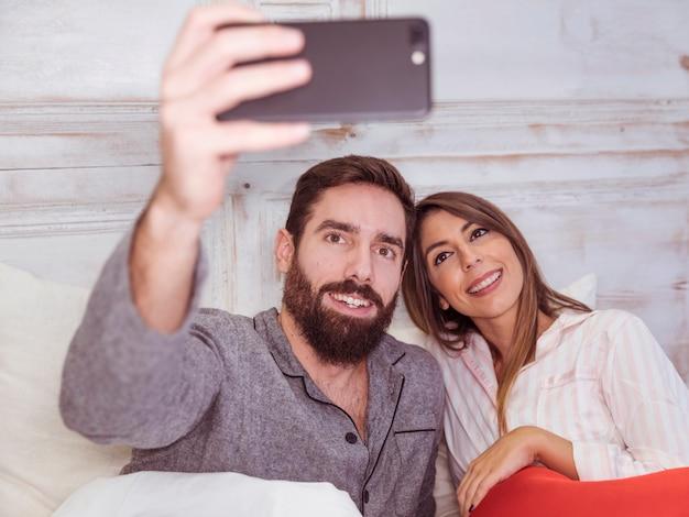 Jeune couple prenant selfie au lit