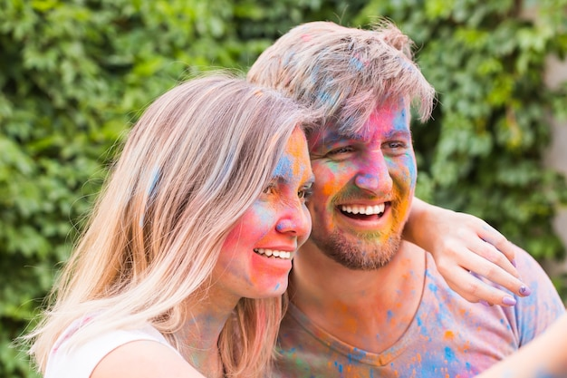 Jeune couple prenant selfie dans des vêtements sales colorés