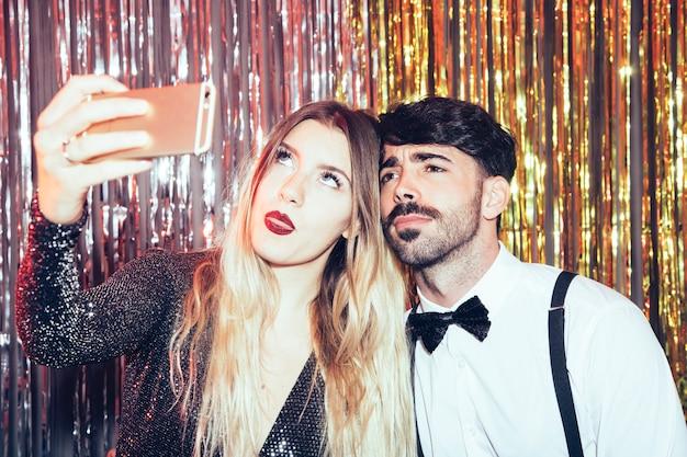 Jeune couple prenant selfie sur la fête du nouvel an