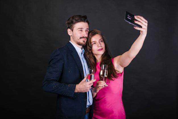 Jeune couple prenant selfie à la fête