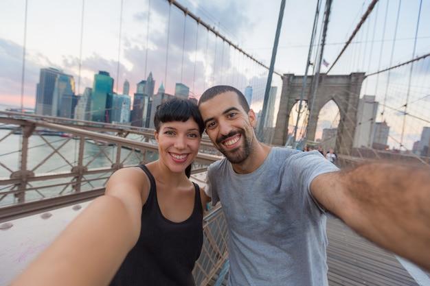 Jeune couple prenant selfie sur le pont de brooklyn