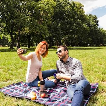 Jeune couple prenant selfie sur téléphone portable au pique-nique en plein air