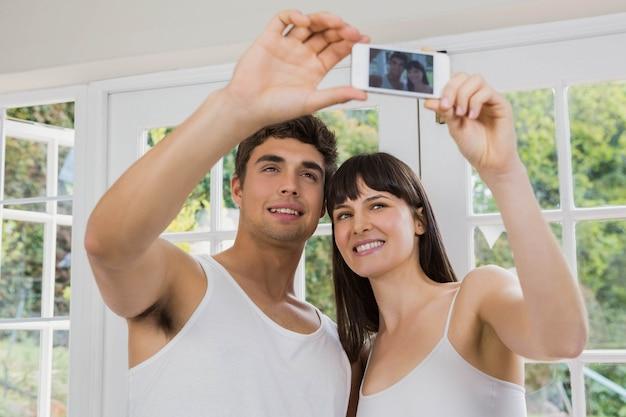 Jeune couple prenant un selfie sur téléphone portable dans le salon