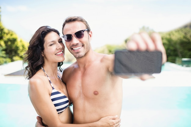 Jeune couple prenant selfie avec téléphone portable près de la piscine