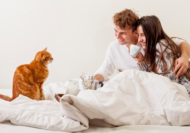 Jeune couple prenant son petit déjeuner au lit