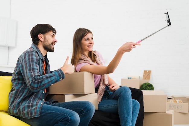 Jeune couple prenant des sulfures avec un smartphone dans leur nouvelle maison
