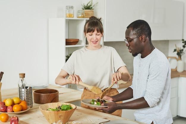 Jeune couple préparant une salade de légumes ensemble dans la cuisine