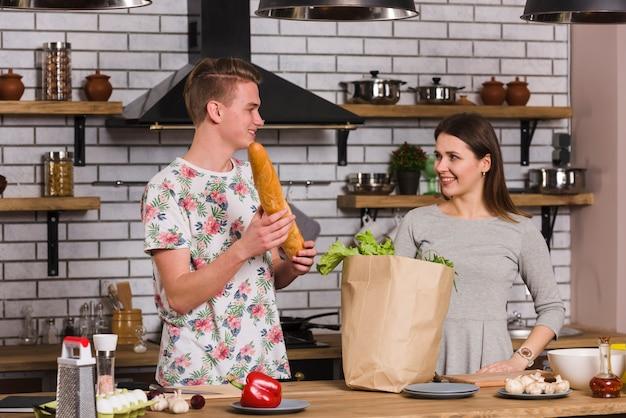 Jeune couple prépare des ingrédients pour la cuisine