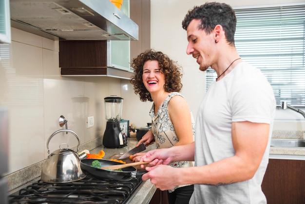 Jeune couple prépare des légumes dans la cuisine