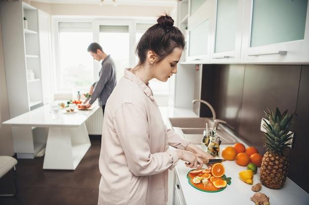 Jeune couple prépare le petit déjeuner ensemble en coupant des fruits dans la cuisine